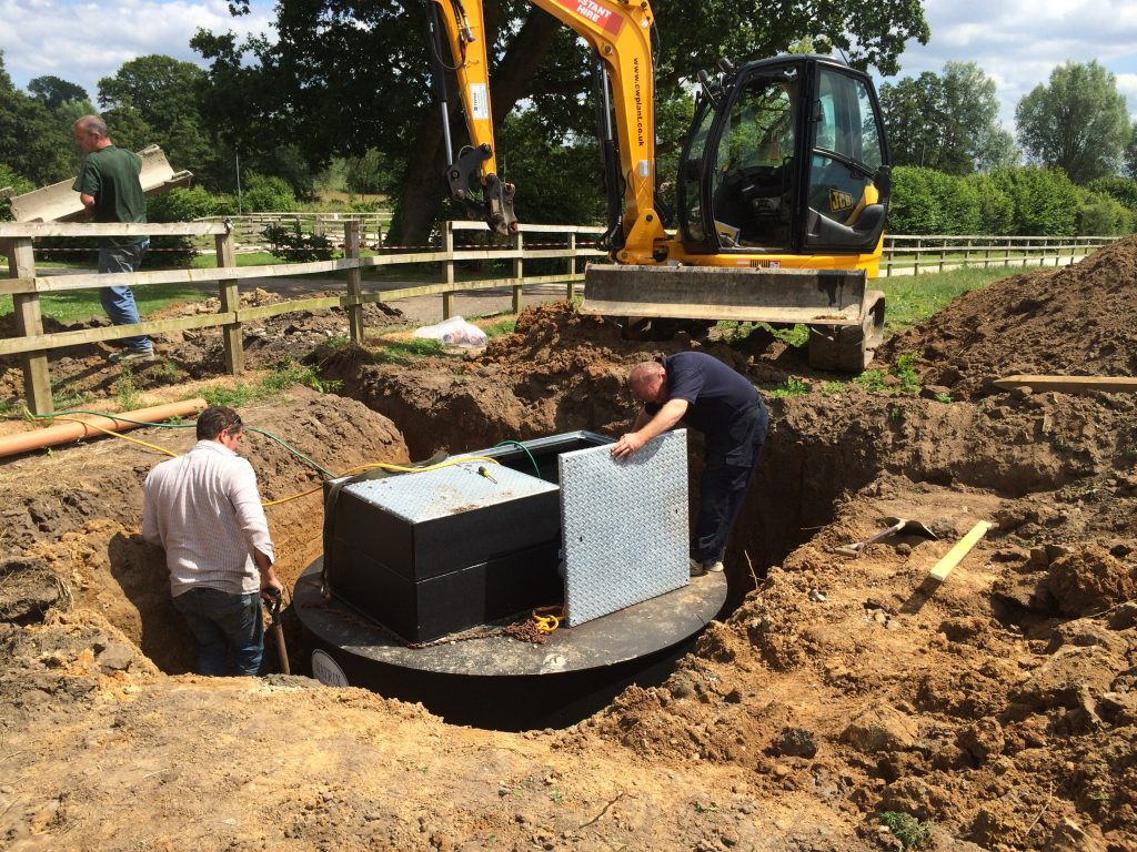 Excavator installing drainage tank